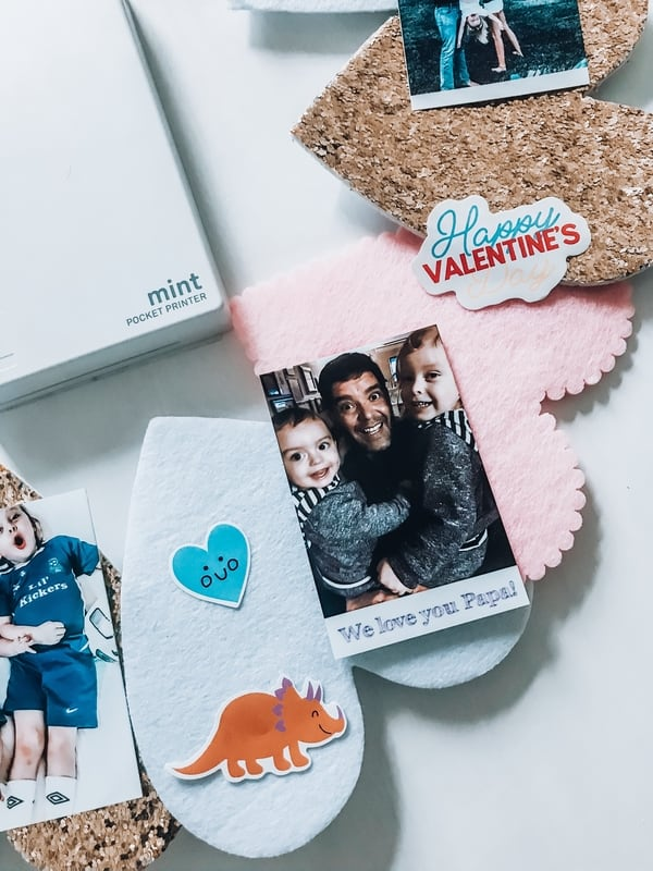 A Polaroid photo of a father with his two children next to Valentine's Day art supplies, and a Polaroid Mint Pocket Printer