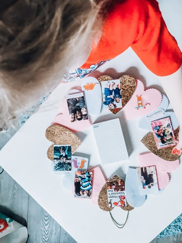 Collage of family Polaroid photos and paper hearts arranged in a circle around a Polaroid Mint Pocket Printer