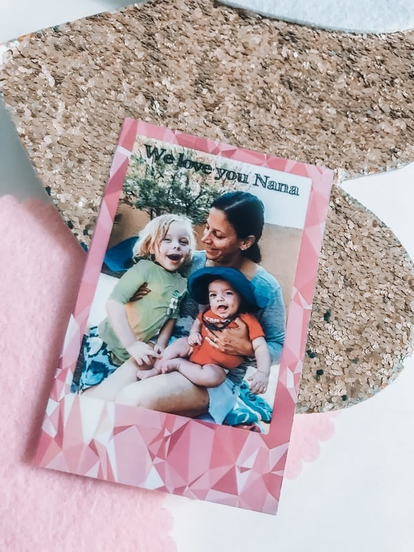 Polaroid photo, of a grandmother and her grandchildren printed with a geometric pink pattern, on top of a sequin gold heart