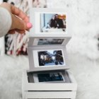 A white wooden box containing an accordion style Polaroid photo album