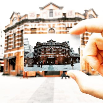 Hand holding a Polaroid picture of The Red House Theater in Taipei, in front of the actual Red House Theater