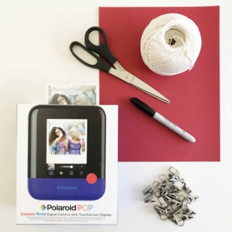 Polaroid POP box next to miscellaneous art supplies
