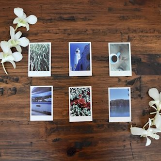 6 Polaroid travel photos laid out on hardwood floor next to white flowers