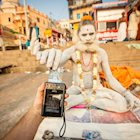 Aghori man taking a printed Polaroid photo from the photographer's Polaroid camera