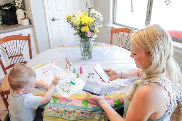 Photo of Jessica Dowd taking pictures with her son drawing on a table
