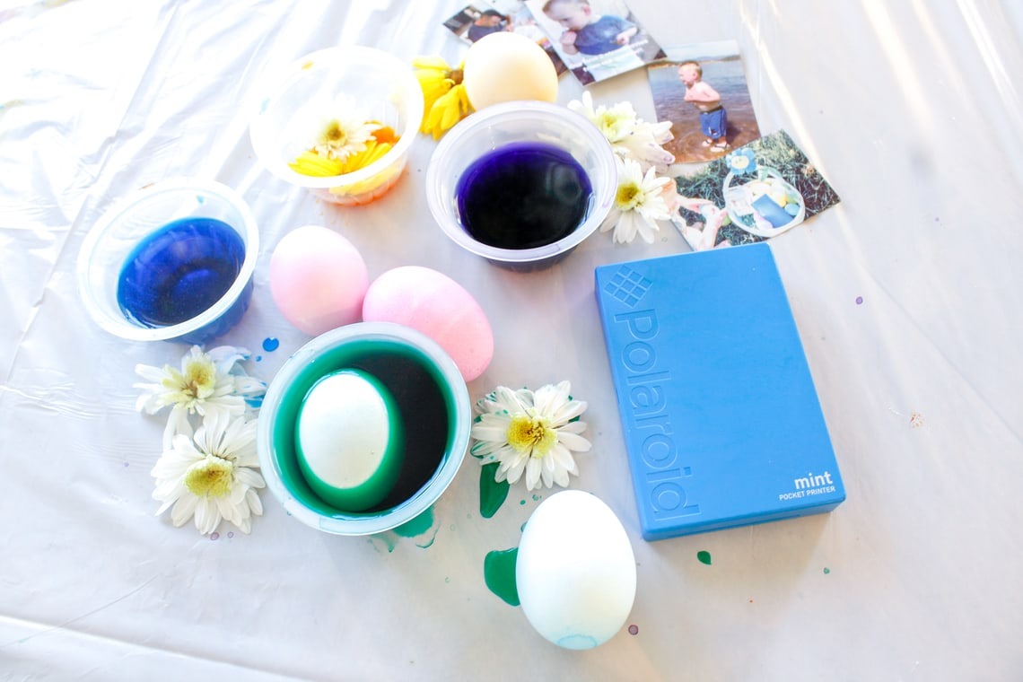 Photo of a flaylay of different dye dishes with eggs in them next to flowers and the Polaroid Mint Instant Digital Pocket Printer