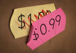 46077653 - psychological pricing printed on a pink label over a normal price. concept image for illustration of prices psychological impact.