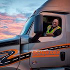 A Schneider driver leans out of a semi-truck window at sun rise.