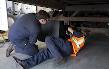 Two diesel mechanics work to fix a brake on a semi-truck.