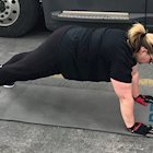 Female truck driver performing push ups