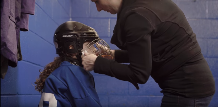 parent taking helmet off kid ice hockey | Source For Sports